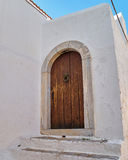 Brown door on white wall. Solid wood brown door on white wall Stock Images