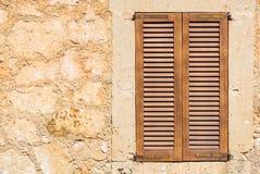 Brown drewniana nadokienna żaluzja z nieociosanym kamiennej ściany tłem fotografia stock