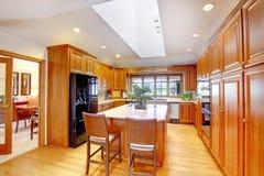 Brown drewniany kuchenny wnętrze z czarnym obmurowanym fridge i biały sufit z skylight Zdjęcia Stock