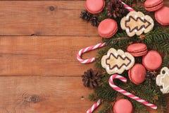 Brown drewniany tło z gałąź świerczyna, macaroons i karmel kije, obrazy stock