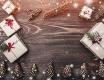 Brown drewniany tło z jedlinowymi rożkami, handmade prezenty z kartka z pozdrowieniami przestrzenią dla zimy, xmas, nowy rok i bo Obrazy Royalty Free