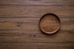Brown drewniany talerz na nieociosanym stołowym zbliżeniu horyzontalny wierzchołek fotografia royalty free