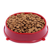 Brown dry cat or dog food in red bowl isolated on white backgrou Royalty Free Stock Images