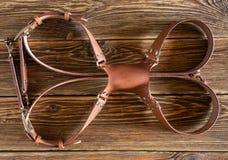 Brown dual camera harness, multi-camera strap harness, leather camera strap on brown wooden background. Royalty Free Stock Photos