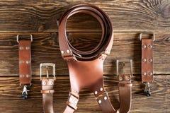 Brown dual camera harness, multi-camera strap harness, leather camera strap on brown wooden background. Stock Photography