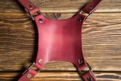 Brown dual camera harness, multi-camera strap harness, leather camera strap on brown wooden background. Royalty Free Stock Image