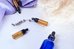 Brown e garrafas azuis do óleo essencial com alfazema seca Imagem de Stock Royalty Free