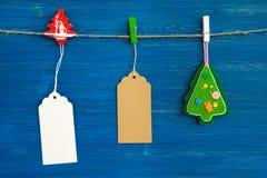 Brown e grupo branco dos preços ou de etiquetas do papel vazio e decoração do Natal que pendura em uma corda no fundo azul Foto de Stock Royalty Free