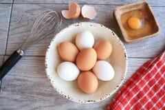 Brown e ovos brancos na bacia e no wisk brancos Imagem de Stock Royalty Free