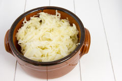 Brown earthenware bowl with raw sauerkraut Stock Images
