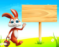 Brown easter bunny stands near wooden sign Royalty Free Stock Image