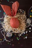 Brown Easter egg in the form of rabbit in the nest with willow branch and quail eggs. Brown Easter egg in form of rabbit in the nest with willow branch and Royalty Free Stock Images