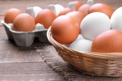 Brown ed il pollo bianco eggs in un canestro di vimini accanto al vassoio dell'uovo su un fondo marrone Fotografia Stock Libera da Diritti