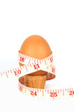 Brown egg on eggcup with measure tape Stock Images