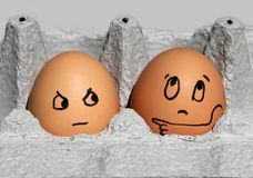 Brown Egg With a Face Pointing, `Pick Him!` Stock Photos