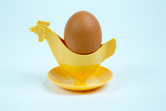 Brown egg in a hen or rooster shaped eggcup Royalty Free Stock Image