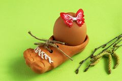 Brown egg with red decorative satin butterfly in brown ceramic shoe with jute cord and birch twigs with earrings on light green stock images