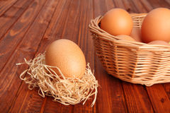 Brown egg in straw nest and in the basket Royalty Free Stock Photos