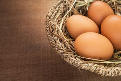 Brown eggs in basket on wooden table Royalty Free Stock Image