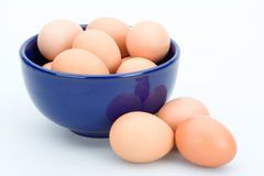 Brown eggs in the blue bowl, isolated Stock Photo