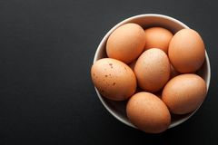 Brown eggs in bowl isolated on dark background Royalty Free Stock Images