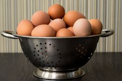 Brown eggs in a bowl on a wooden table. Chicken egg in metal sieve.  Concept of organic farm products Stock Photo