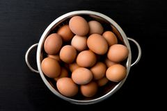 Brown eggs in a bowl on a wooden table. Chicken egg in metal sieve.  Concept of organic farm products Stock Image