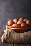 Brown eggs in a brown ceramic bowl on sacking and wooden table on an gray abstract bbackground. Rustic Style. Eggs.  Easter photo. Concept. Copyspace Royalty Free Stock Image