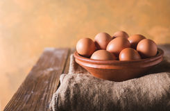 Brown eggs in a brown ceramic bowl on sacking and wooden table on an orange abstract bbackground. Rustic Style. Eggs. Royalty Free Stock Photography