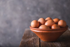 Brown eggs in a brown ceramic bowl on  wooden table on an gray abstract bbackground. Rustic Style. Eggs.  Easter photo concept Stock Photos