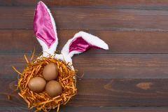 5912ce440df Brown eggs in a decorative nest with bunny ears on a wooden background  stock photography