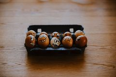 Brown eggs with different faces expressions painted on egg shell Stock Photo
