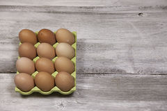 12 Brown Eggs. A dozen farm fresh brown eggs on a white washed rustic background Royalty Free Stock Photo