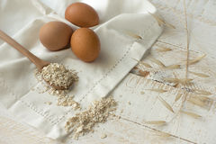 Brown eggs,dry oatmeal flakes on wooden spoon scattered over white linen cloth, wood background Royalty Free Stock Photography