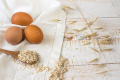 Brown eggs,dry oatmeal flakes on wooden spoon scattered over white linen cloth, wood background, healthy ingredients Royalty Free Stock Photos