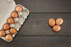 Brown eggs in egg carton. On a dark wooden table Stock Photo