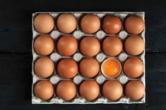 Brown eggs and egg yolk in carton box. On black background stock image
