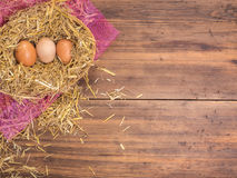 Brown eggs in hay nest. Rural eco background with brown chicken eggs and straw on the background of old wooden planks Royalty Free Stock Photography