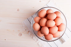 Brown eggs in a large glass bowl on a light wooden table view. Brown eggs in a large glass bowl on light wooden table view Stock Images