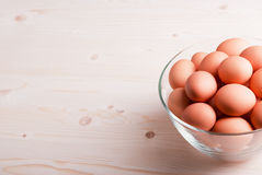Brown eggs in a large glass bowl on a light wooden table view Royalty Free Stock Photo