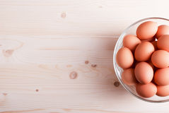 Brown eggs in a large glass bowl on a light wooden table view Royalty Free Stock Photography