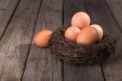 Brown Eggs in a Nest. On a wood surface stock photos