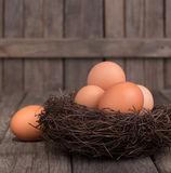 Brown Eggs in a Nest. On a wood surface royalty free stock image