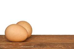 Brown Eggs on Old Timber over White. Two brown eggs on old timber, over white background.  Lots of copy space Stock Photos
