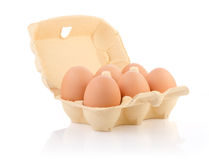 Brown eggs in the package. Six brown eggs in carton on white with clipping path Royalty Free Stock Image