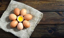 Brown eggs on a sack in a circle with open egg in middle on wood stock photo