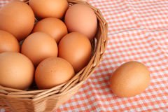 Brown eggs on vintage tablecloth and in the basket Stock Photos