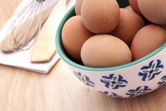 Brown Eggs in a White and Blue Bowl on a wooden background Stock Photography