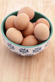 Brown Eggs in a White and Blue Bowl on a wooden background Stock Images