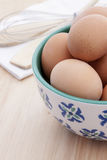 Brown Eggs in a White and Blue Bowl on a wooden background Royalty Free Stock Photography